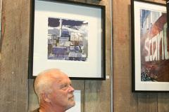 Sjömannen och konstnären Lars ʺMellisʺ Melander under några av sina verk i montern.